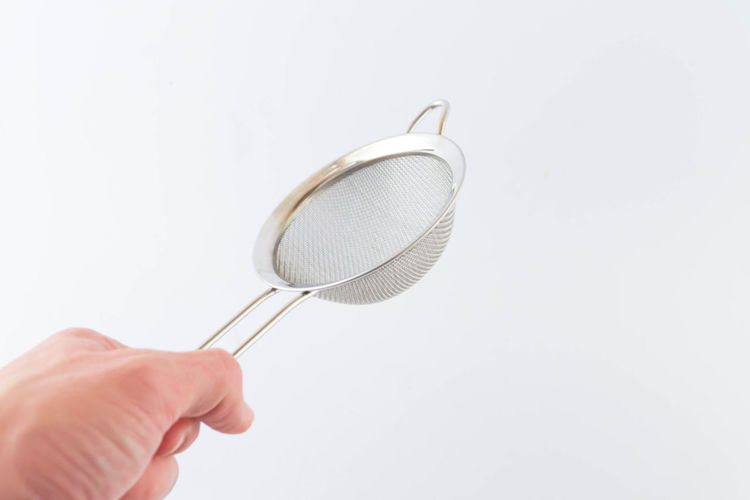 Close-up of hand holding strainer over white background