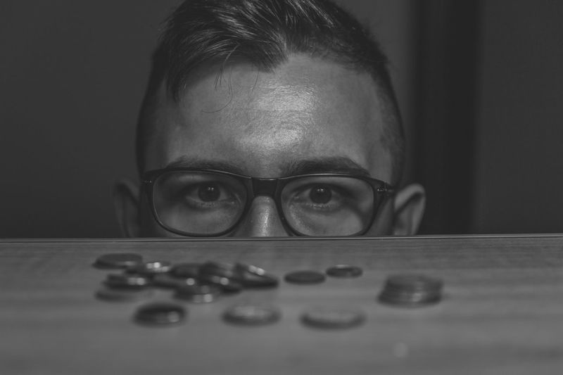 Cropped image of man by coins at table