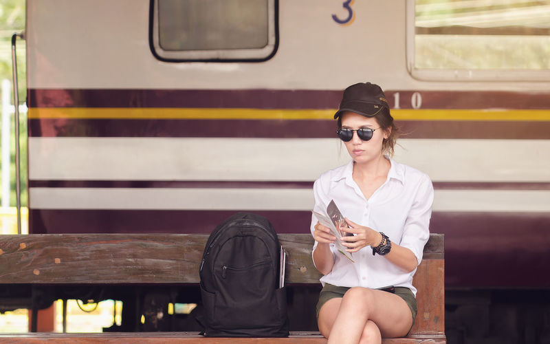 Young woman holding brochure while sitting on bench at railroad station