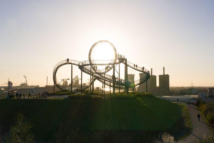 Ferris wheel in park against sky during sunset