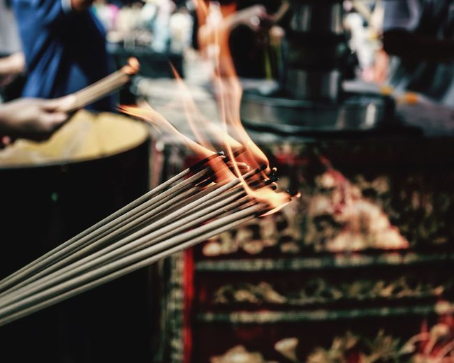 Close-Up Of Lit Incense Sticks In Temple