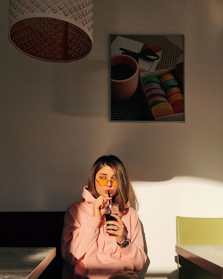 Young woman drinking cola at restaurant