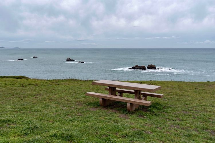 Landscape of picnic table on grass above the Pacific Ocean in Oregon Oregon Coast Oregon Picnic Table Sea Water Horizon Over Water Sky Horizon Beauty In Nature Scenics - Nature Land Beach Tranquility Tranquil Scene Nature Plant No People Day Seat Idyllic Outdoors Grass Cloud - Sky