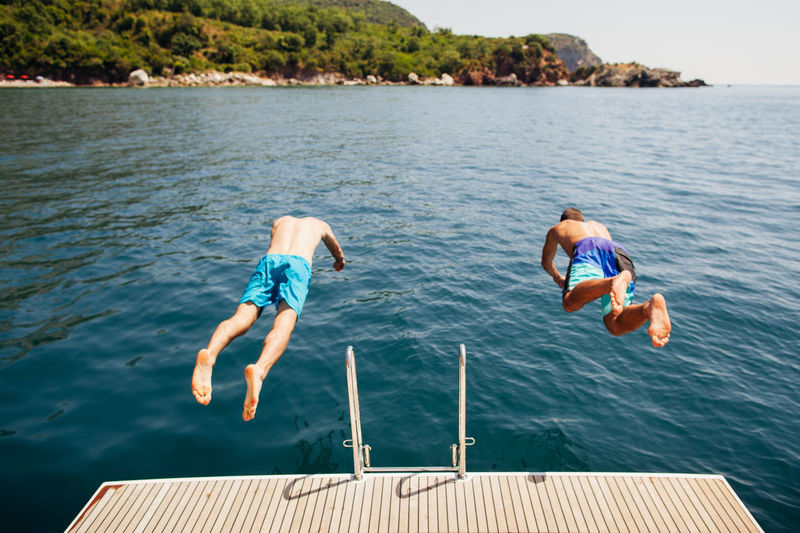 People jump in the water from yacht. Leisure activity EyeEm Best Shots EyeEm Gallery Fun Luxurylifestyle  Summertime Swimming Adult Adventure Jump In The Water  Jumping Leisure Leisure Activity Lifestyles Men Outdoors People Real People Sea Seascape Swimming Togetherness Two People Vacations Water Yachting