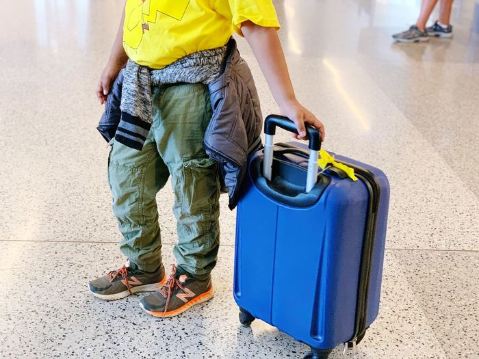 Kid traveling alone unaccompanied minor Real People One Person Low Section Casual Clothing Men Lifestyles Day Human Body Part Jeans Luggage Shoe Women Human Leg Body Part Adult Outdoors Nature Standing Travel