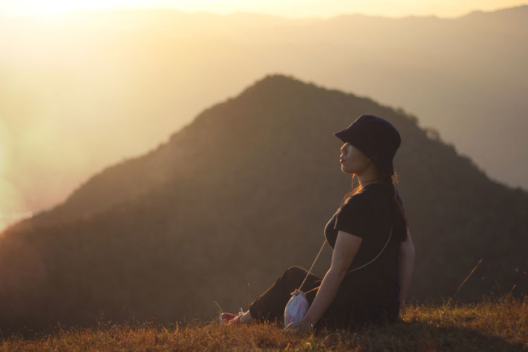 Woman looking away while sitting on mountain during sunset