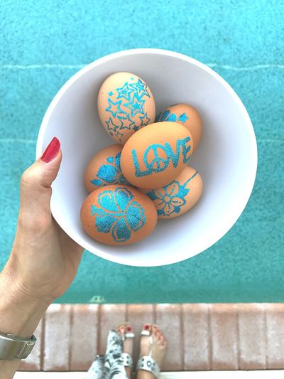 Close-Up Of Hand Holding Painted Easter Eggs In Bowl