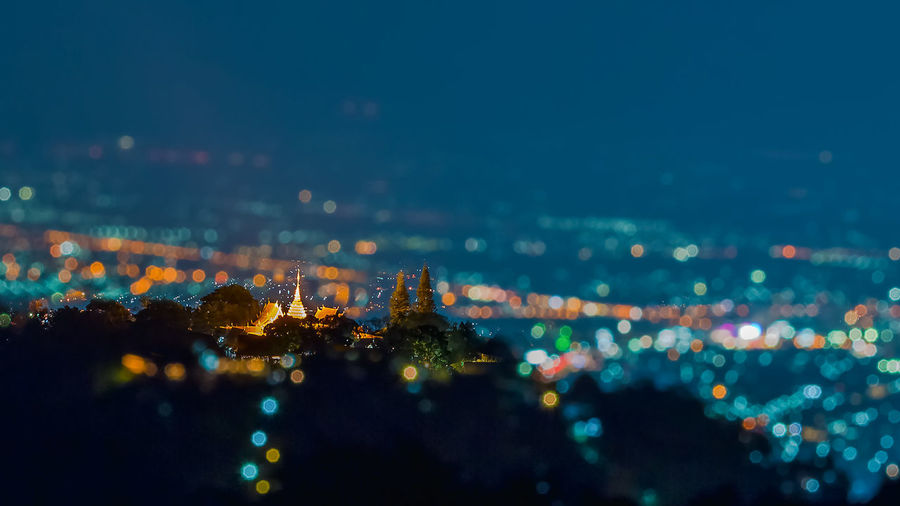 Tilt-shift image of wat phra that doi suthep in illuminated city at night
