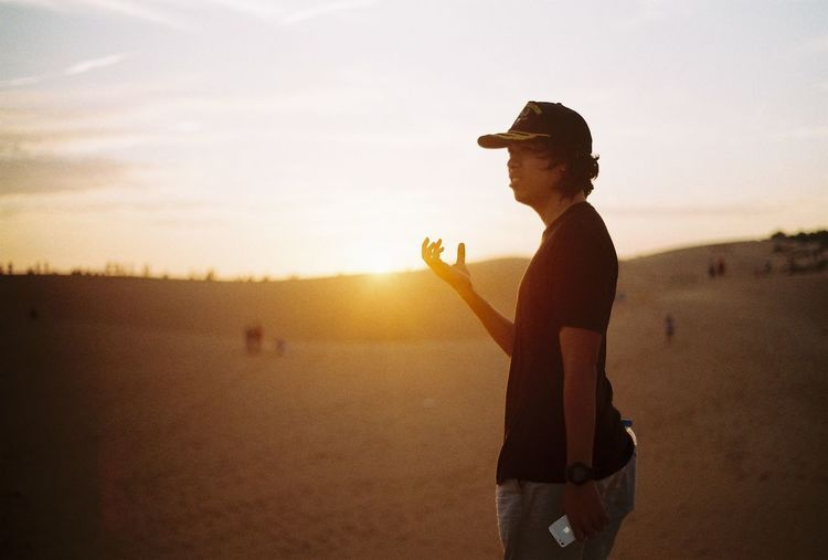 Young man arm raised try to hold the sunrise in the desert 35mm Film Man Bad Habit Beach Beauty In Nature Boy Day Film Photography Grain Leisure Activity Lifestyles Nature One Person Outdoors People Real People Side View Silhouette Sky Standing Sun Sunset Young Adult