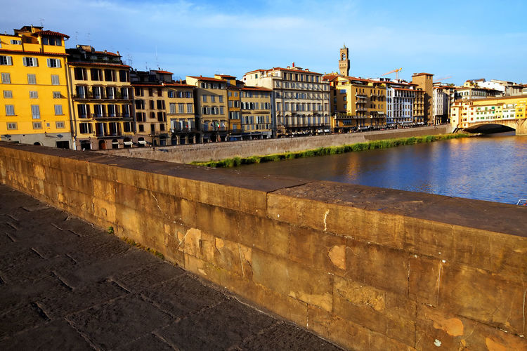 Buildings By Arno River Seen From Ponte Santa Trinita In Tuscany