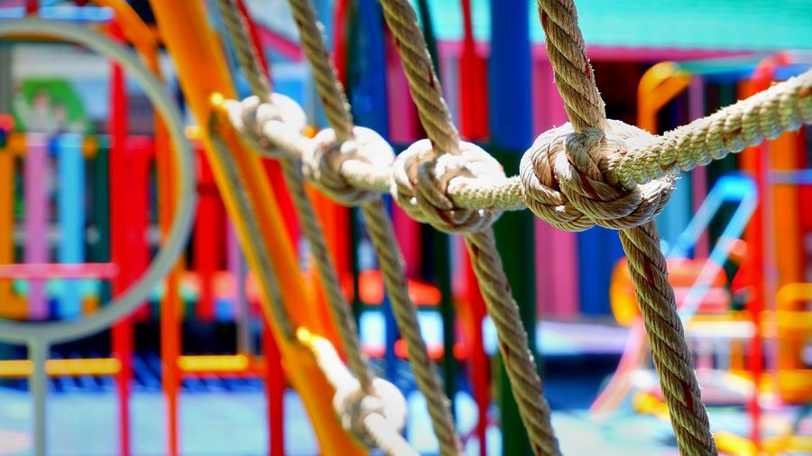 Focus on rope mesh and blurred colorful outdoor play equipments in playground area of kindergarten school Colorful Area Objects Kindergarten School Pattern Old Empty Nobody Childhood Kids Decorations Materials Metal Foreground Mesh Outdoor Play Equipment Playground Jungle Gym Swing Slide EyeEm Selects Hanging Rope Multi Colored Close-up Monkey Bars