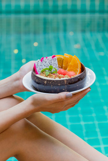 Woman holding smoothie bowl with fresh fruits by swimming pool