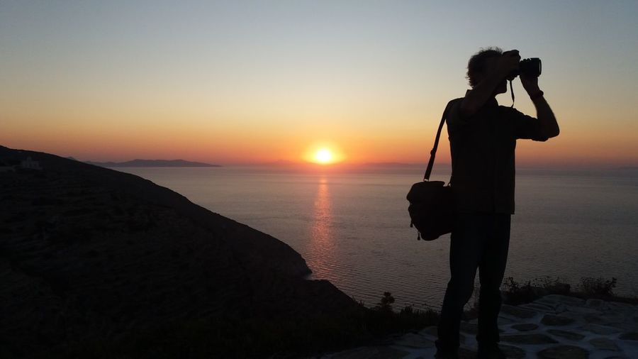Man photographing through camera while standing against sea during sunset