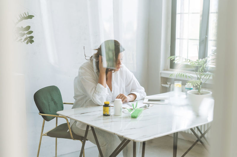 Thinking brunette woman doctor nutritionist plus size in white shirt working on table
