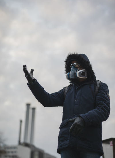 Man with mask photographing against sky after corona influenza in berlin 2020