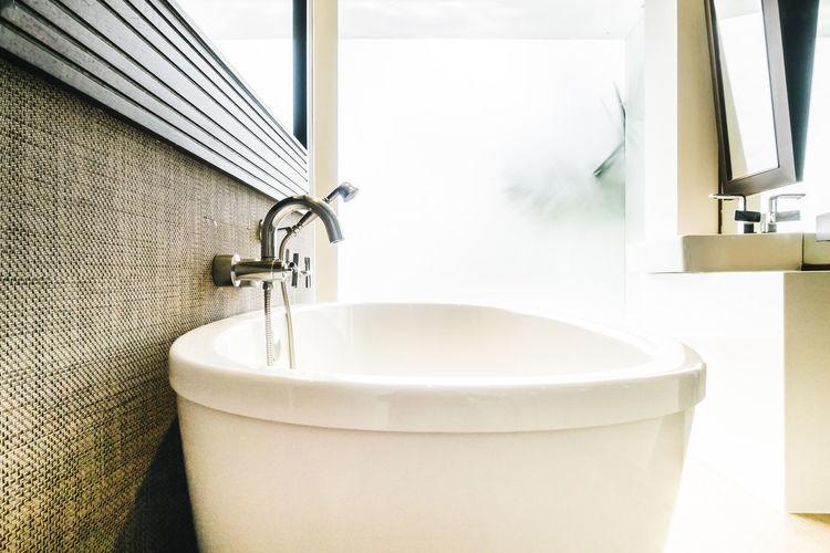 Porcelain wash bowl below mirror in bathroom