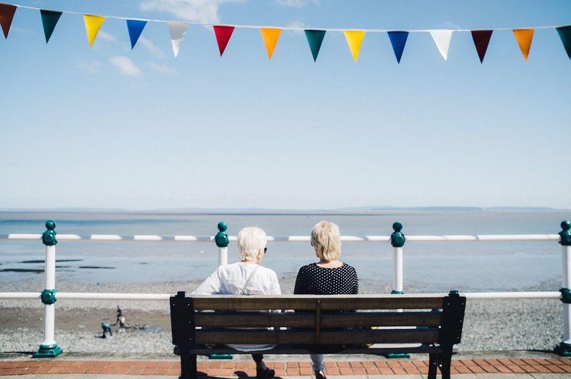 Rear View Of Senior Women Sitting On Bench