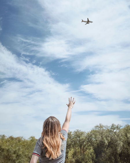Rear View Of Woman Gesturing Towards Airplane Flying Against Sky