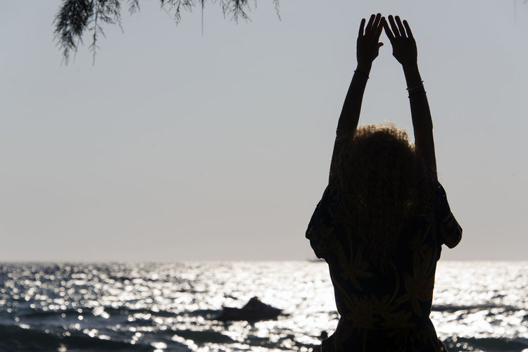 SILHOUETTE OF People playing, swimming in the waves in the island of Patmos, Greece in summer time Adult Arms Raised Beach Beauty In Nature Hairstyle Horizon Horizon Over Water Human Arm Land Leisure Activity Lifestyles Nature One Person Outdoors Real People Rear View Scenics - Nature Sea Sky Standing Water Women