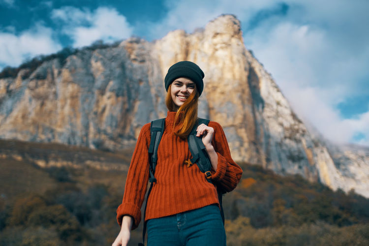 Young woman wearing hat standing against mountain during winter