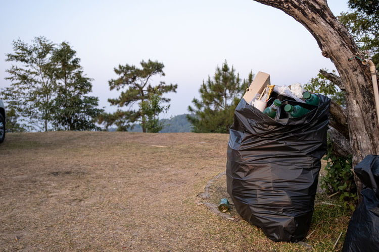 Close-up of garbage in bag on field
