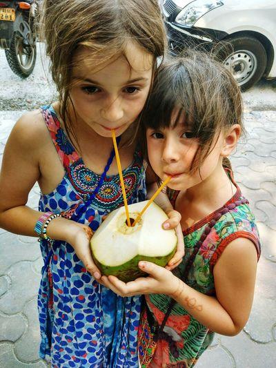 Cute sisters drinking coconut water on footpath