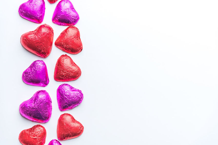 Chocolate valentine hearts wrapped in red and pink foil on left side of white background Bright Chocolate Chocolate Hearts Fun Happy Holiday Love Minimalist Romance Romantic Valentine Valentine Candy Valentine's Day  White Space Candy Copy Space Food Minimal Minimalism Pink Hearts Red Hearts Simple Simplicity Symbol White Background