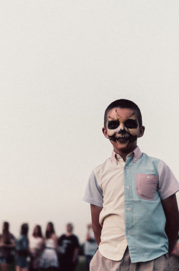 Portrait of boy with evil face paint against sky