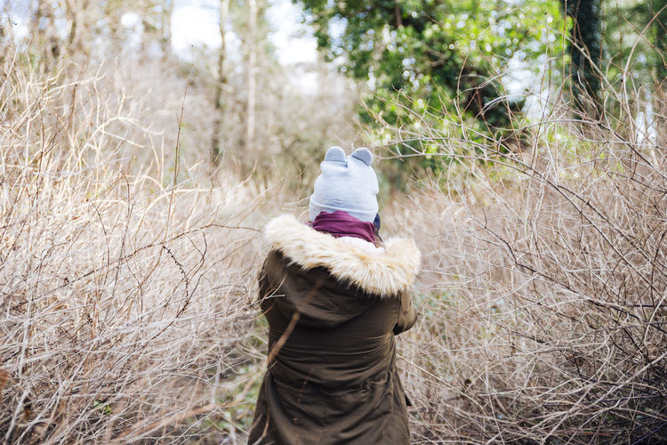 Rear View Of Woman Standing In Forest During Winter