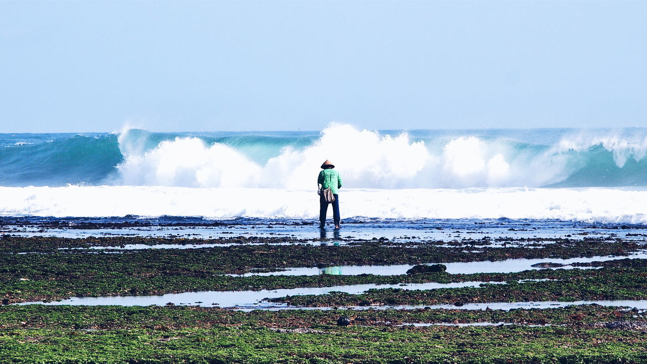 Rear view of a man overlooking waves at sea