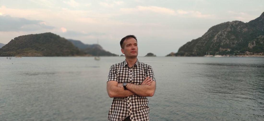Portrait of man standing in sea against sky