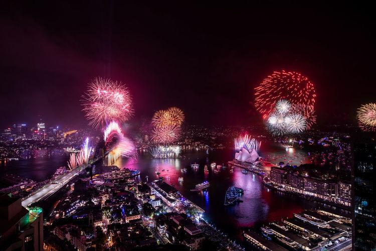 Firework display in illuminated city at night