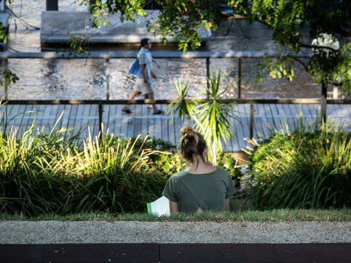 Rear view of woman sitting by plants