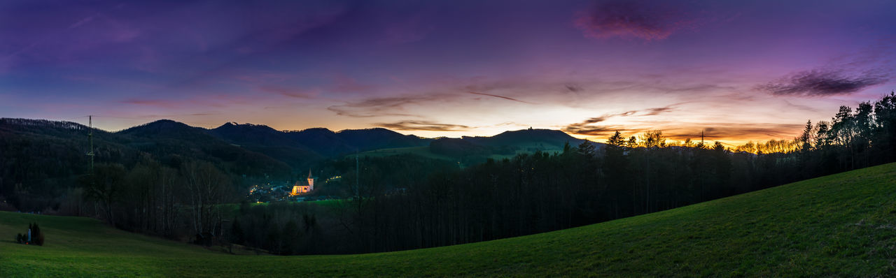 Panoramic view of green landscape and mountains at sunset