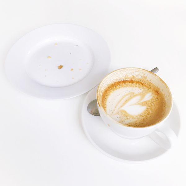 EyeEm Selects Drink Coffee Cup Coffee - Drink Frothy Drink Refreshment Food And Drink Saucer Cappuccino Table White Background No People Froth Art Freshness Close-up Studio Shot Latte Indoors  Food Healthy Eating Day Half finished coffee and plate with pastry crumbs