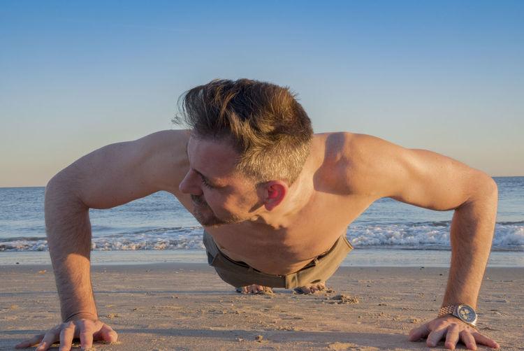 Shirtless man exercising at beach