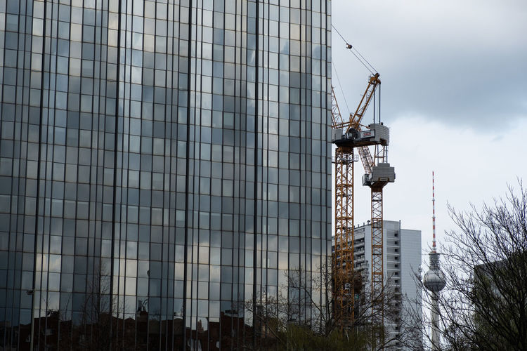Construction site by buildings against sky in city