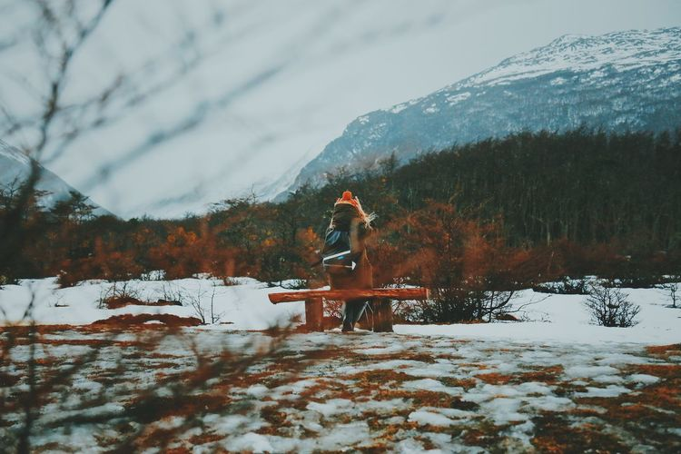 Rear View Of Woman Wearing Warm Clothing While Sitting On Bench Against Mountains
