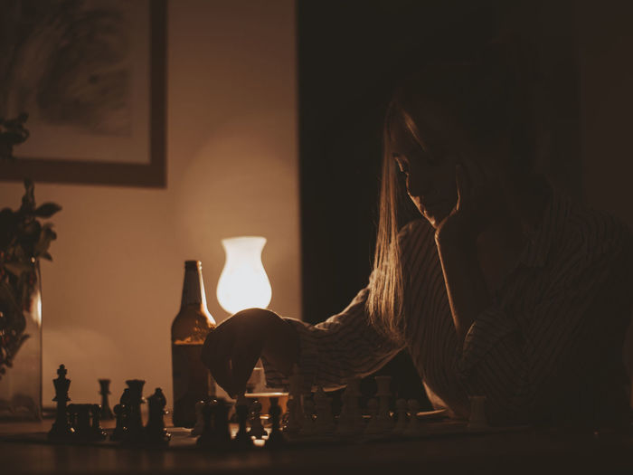 Midsection of woman with wine bottles on table at home