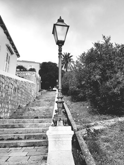 Street light by footpath in park against sky