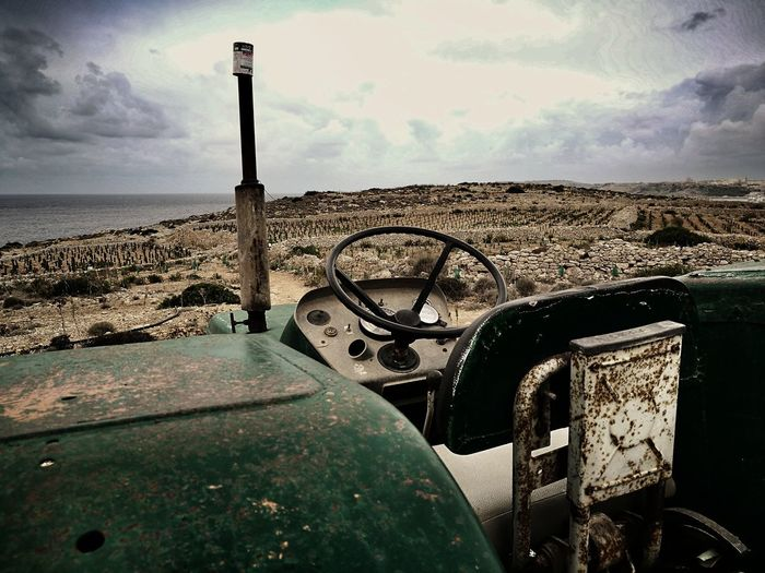 Abandoned car on field by sea against sky