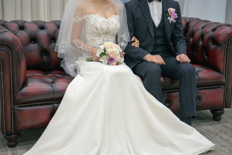 Bride And Groom Sitting On Sofa