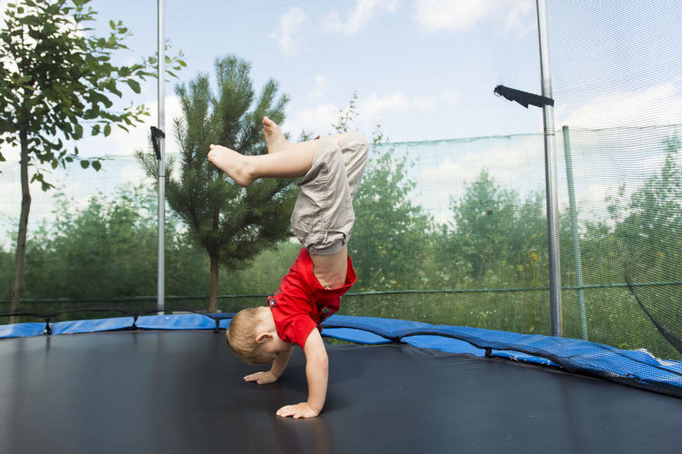Side view of boy practicing handstand on trampoline against trees