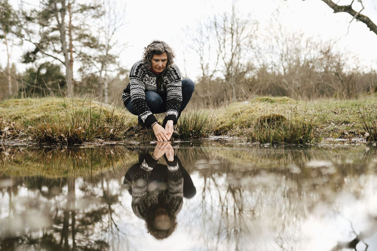 Full length of man with reflection in lake