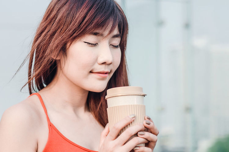 47e83fdf Close up beautiful young woman standing on balcony having cup of coffee,  enjoying sun on · Portrait Of Happy Woman With Tousled Hair Against Gray  Background