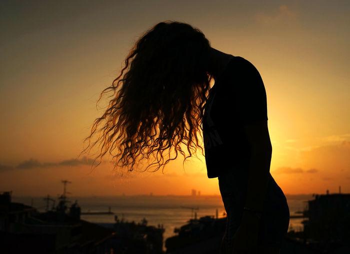 Silhouette woman standing on beach against orange sky
