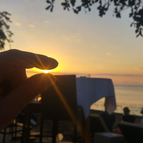 Hand holding sun over sea against sky during sunset