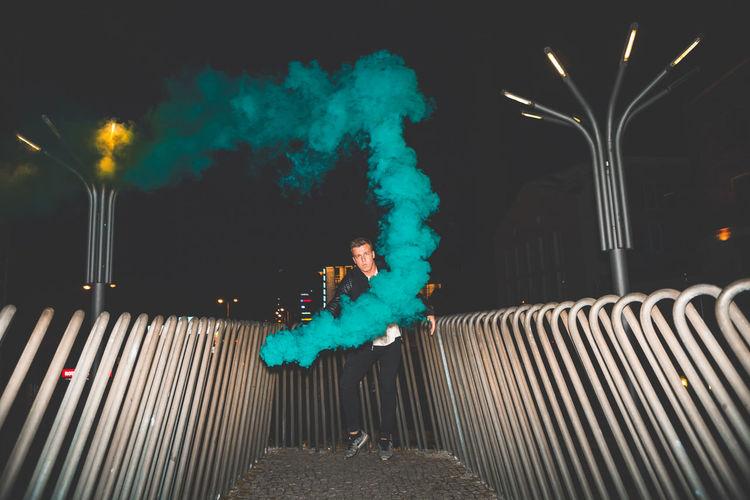 Man with smoke bomb at night