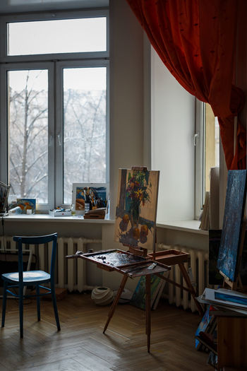 Various artist equipment in the workshop studio. Natural daylight. Table Indoors  Window Seat Chair No People Furniture Day Absence Curtain Domestic Room Flooring Home Interior Transparent Lighting Equipment Glass - Material Wood - Material Empty Home Artisan Artist Art Art Studio Painting Palette