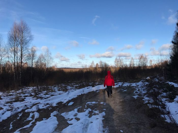 Rear view of person on snowy field against sky during winter